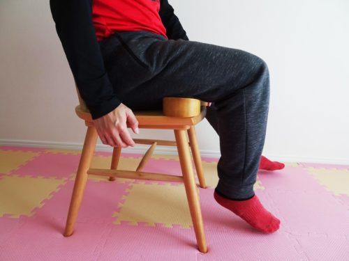 椅子に座って骨盤職人を腿裏に当てている